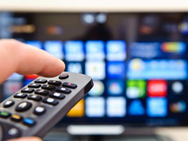 Pessoa apertando tecla controle remoto e TV em segundo plano desfocada.