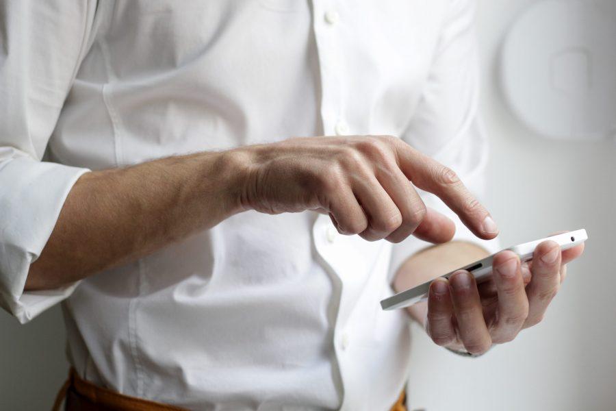 Homem teclando no celular.