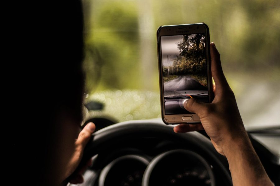 Homem tirando foto com celular, dirigindo carro.