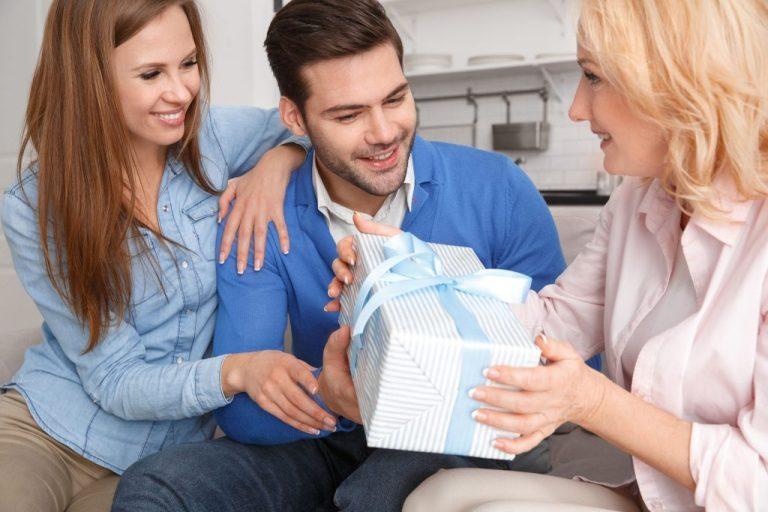Na foto um casal dando um presente para uma mulher.