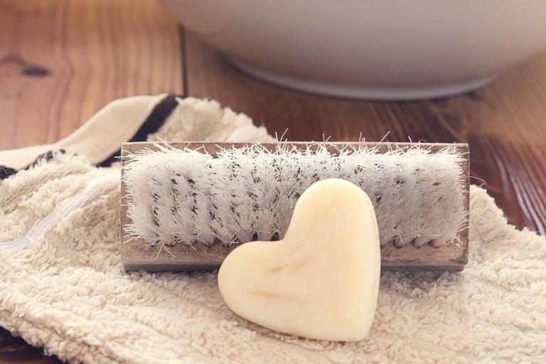 Imagem de sabonete em forma de coração apoiado em escova de banho