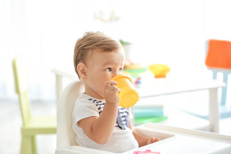 Menino sentado em cadeirinha de alimentação bebendo em seu copinho.