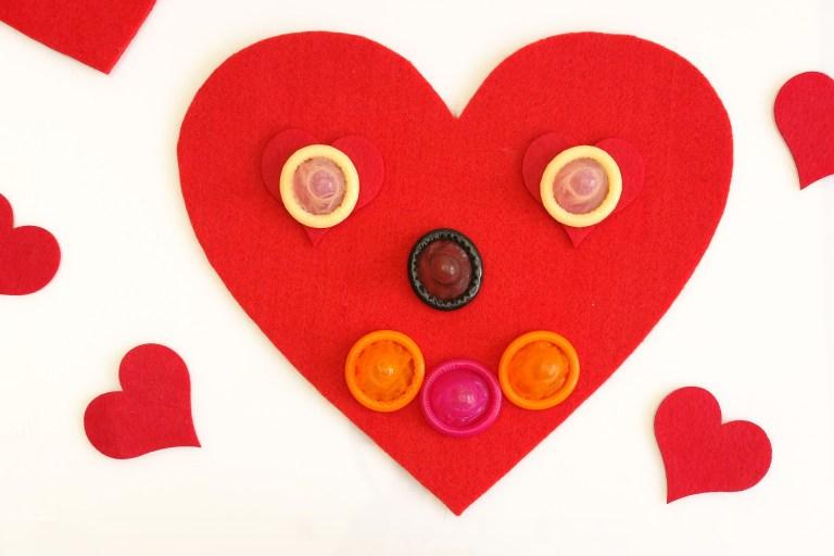 Imagem de várias camisinhas coloridas sobre um coração