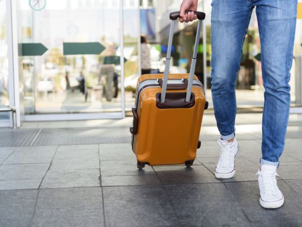 Close up of legs of young man going into the airport with suitcase