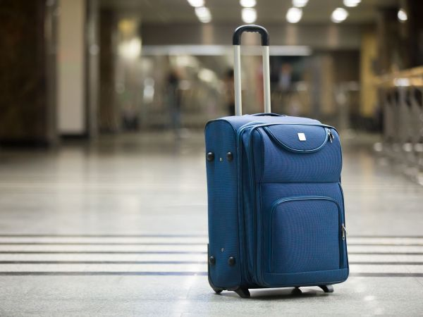 Large blue wheeled suitcase standing on the floor in modern airport terminal. Copy space