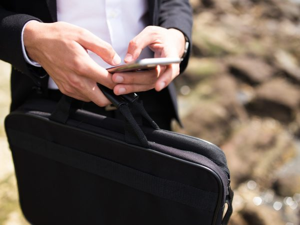 Businessman with briefcase texting message outdoors or checking email. Close-up of unrecognizable man using gadget to surf net. Modern lifestyle concept