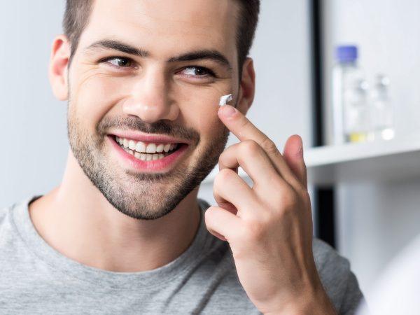 happy man applying facial cream in bathroom while looking at mirror