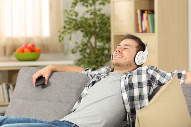 Ragazzi che ascolta la musica sul divano con le cuffie