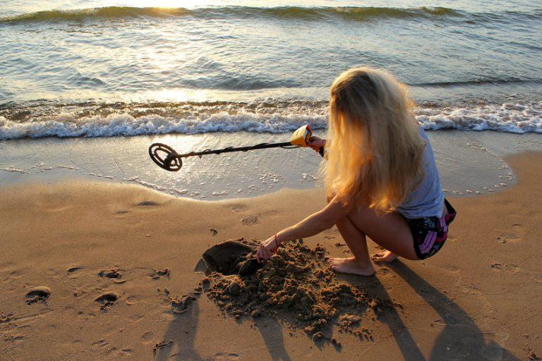Ragazza con il metal detector in spiaggia
