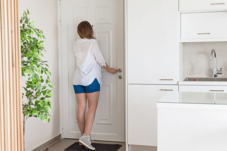 Donna che guarda dallo spioncino della porta