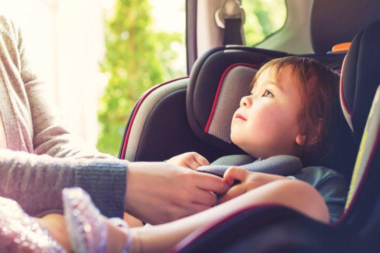 Mamma che sistema la bimba nel seggiolino auto