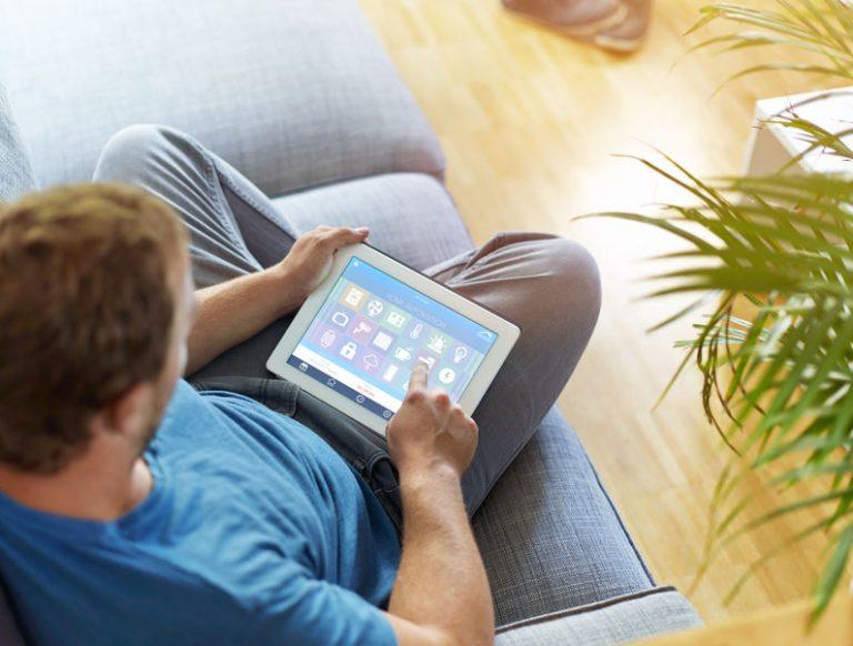 Uomo seduto sul divano con il tablet