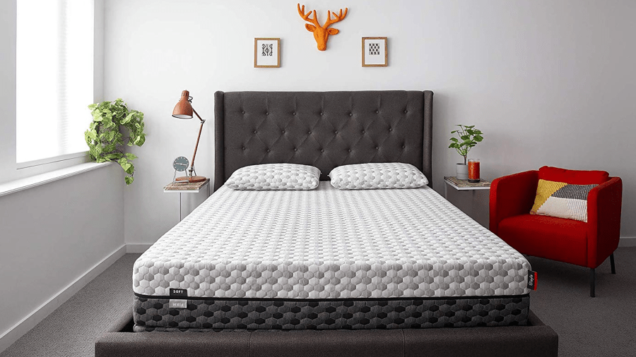 Layla foam mattress in a stylish bedroom next to a red chair