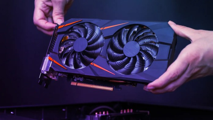 Hands holding a graphics card against dark background