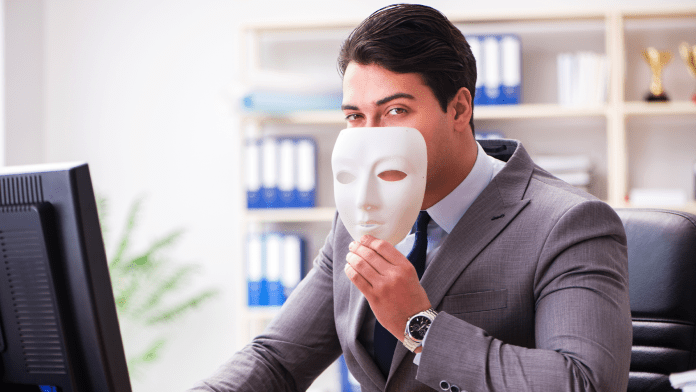 A photo of a businessman wearing a plastic mask.