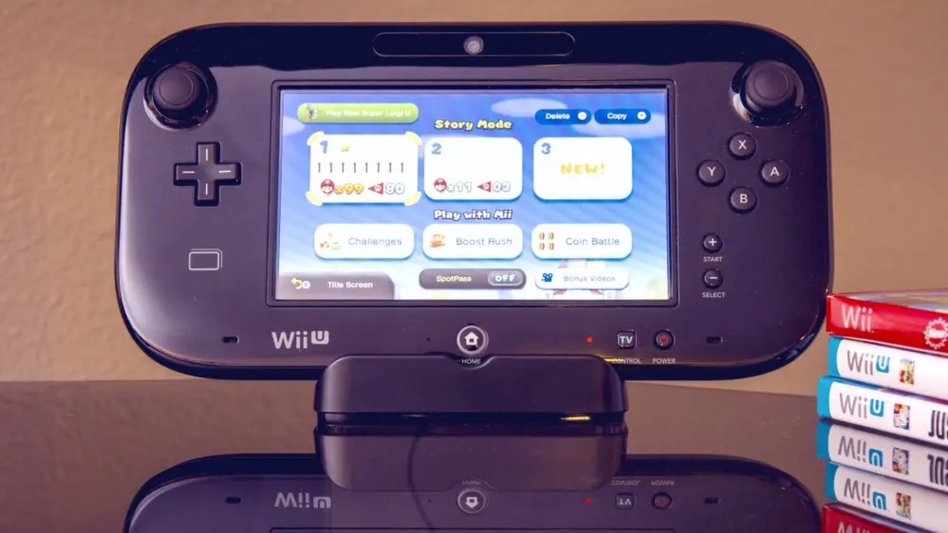 Wii U gaming console on shiny table with Wii U games next to it