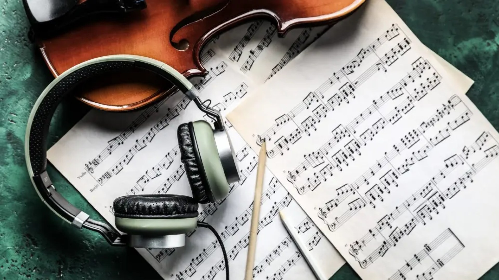violin, headphones, and sheet music on table