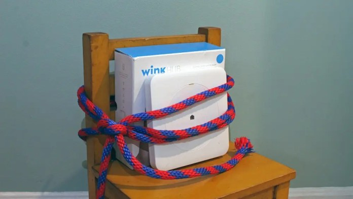 A Wink Hub and box tied to a chair, as if being ransomed.