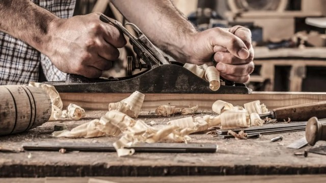 A man planing a piece of oak on a workbench.