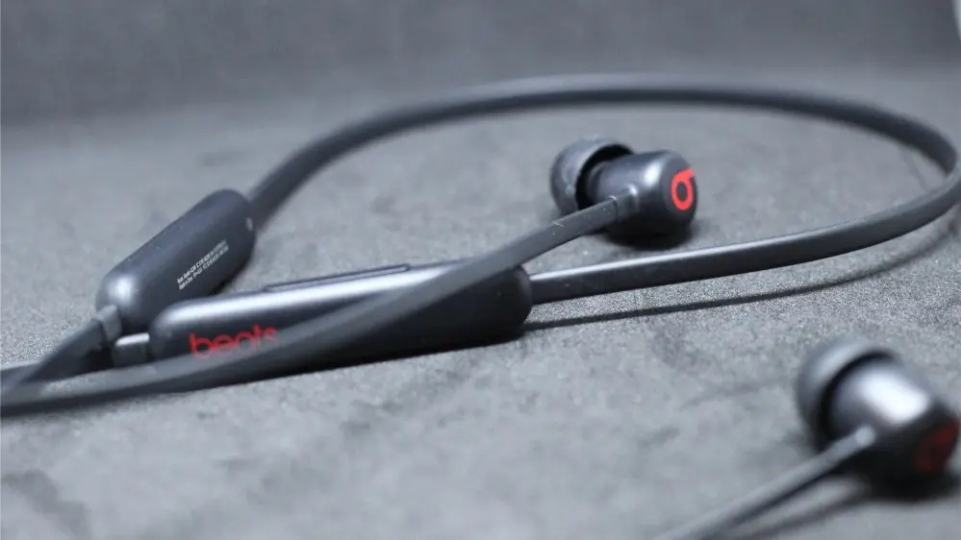 The Beats Flex in black on a black matte background, one earbud and the Beats logo in focus