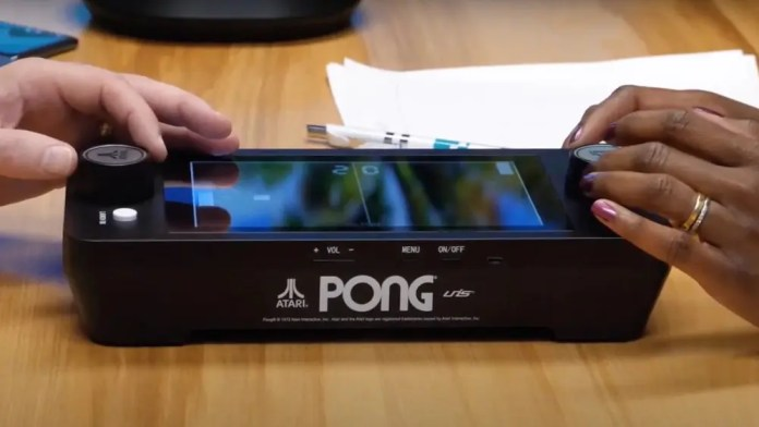 Arcade1Up Mini Pong machine being played by two people on a table