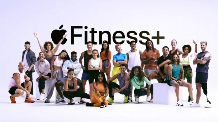 A large group of exercise trainers standing in front of the Apple Fitness+ logo