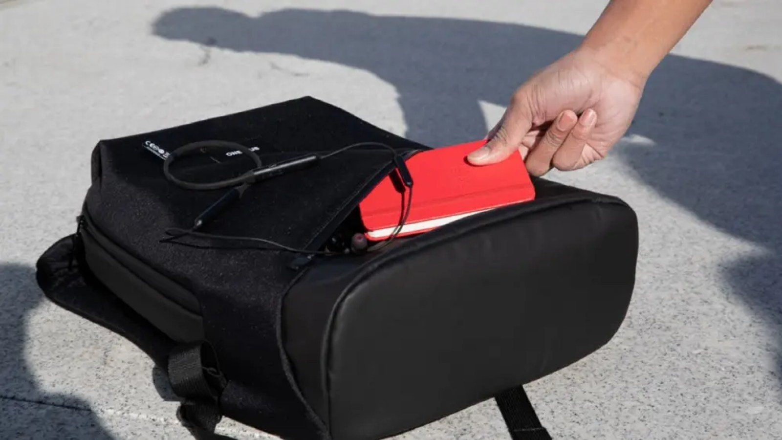 Someone inserting a notebook into the Urban Traveler backpack.