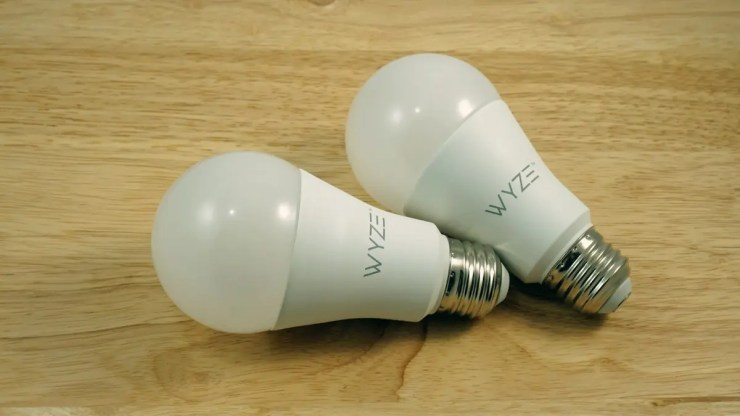 Two Wyze Smart Bulbs on a wooden table.