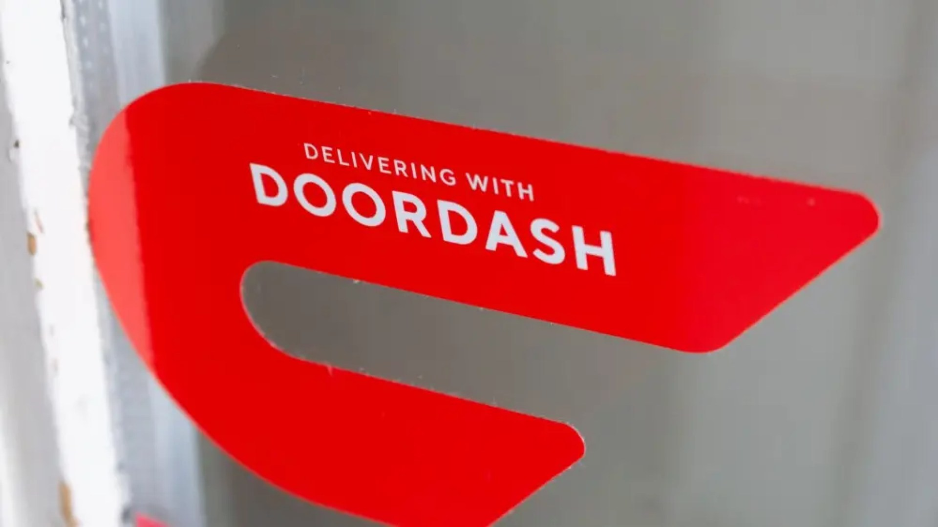 A DoorDash sticker on a window.