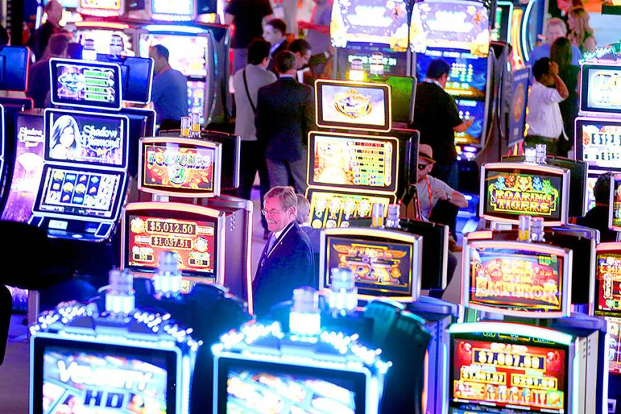 Las Vegas based Scientific Games acquires bingo app maker     Las     People looks at themed slot machines in the Scientific Games booth during  the Global Gaming Expo