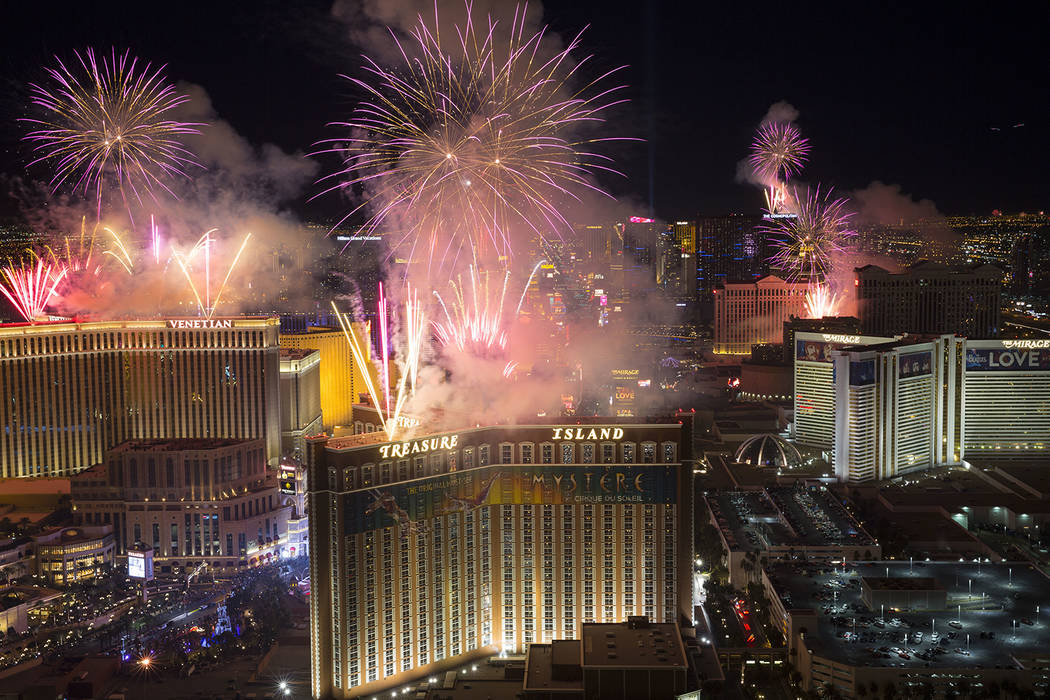 Las Vegas Strip revelers party as police patrol     PHOTOS     Las Vegas     New Year s fireworks are seen along the Strip from the top of the Trump  International