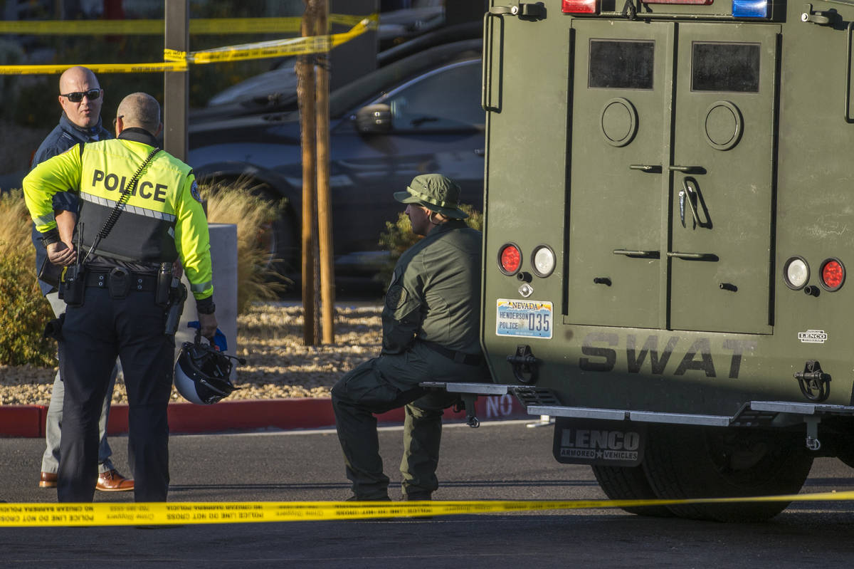 Emergency personnel as well as a SWAT vehicle about the parking lot after four were killed and ...