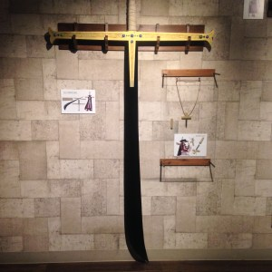 A huge sword with blade black as night and a golden hilt hung at the center of the wall; Dracule Mihawk's cross necklace is hung to the right
