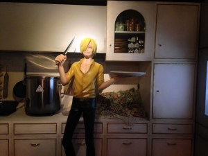 Sanji wearing a yellow shirt standing in front of the kitchen counter with a knife in one hand and a plate in another.