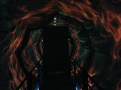 A tunnel of flames with a black door at the center