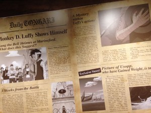 A wall covered with newspaper coverage of Luffy's Marineford message to the rest of the Strawhats and a feature covering Usopp who has gained weight