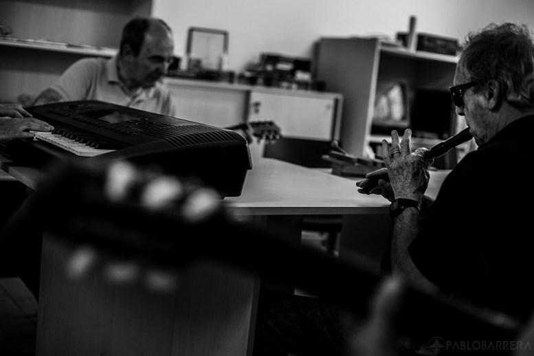 Humberto Richietti ejecuta sonidos con la flauta dulce en la clase semanal de música que se realiza en la Biblioteca Parlante de la ciudad de Mar del Plata, Provincia de Buenos Aires, Argentina. Detrás se encuentra Santiago Duran siguiendo el ritmo con guitarra de la melodía realizada por Humberto. (©Pablo Barrera)
