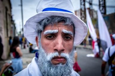 """La figura del """"Gramillero"""" representa distintas tradiciones afrouruguayas. Lleva una valija con yuyos para representar al médico o curandero tradicional. Es anciano porque representa la sabiduría. En su baile tiembla y se toma la cintura. Algunos historiadores lo vinculan con Ansina, médico y mano derecha de José Artigas."""