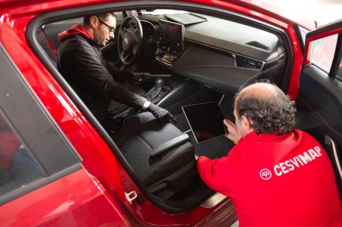 Perito fotografiando el interior de un vehículo.
