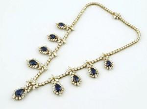 424: GARGANTILLA Realizada en oro, formada por diamantes talla brillante y marquise, peso total aproximado: 19.60 ct., de la que penden nueve zafiros talla perilla, peso total aproximado: 28.10 ct. Se adjunta estuche original.      Salida: 49.300