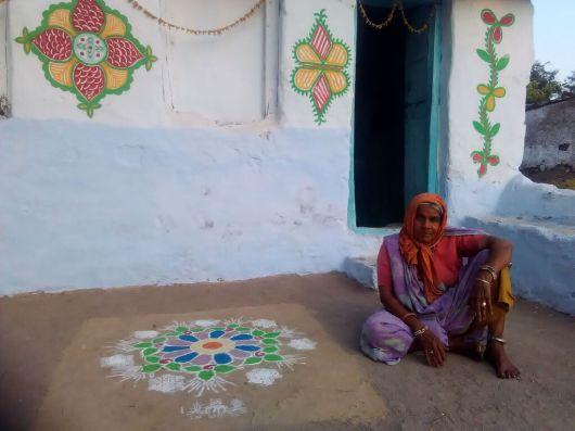 Mulher em frente da casa com mandala de boas-vindas (Mandu)