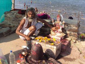 Yogui cuidando da imagem de Shiva nas margens do rio na ilha sagrada de Omkareshwar
