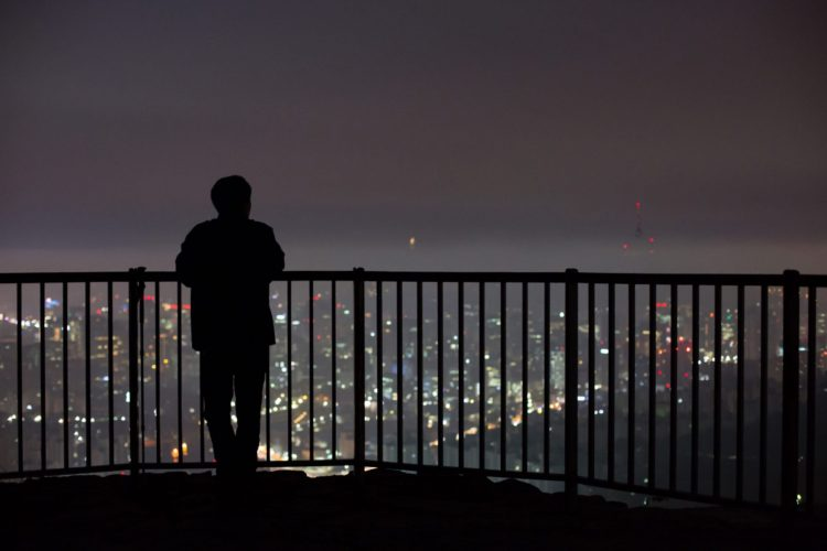 A man looks out at the city skyline shrouded in haze from an observation deck of Ansan mountain at dawn in Seoul, South Korea, on Wednesday, Oct. 7, 2015.  Photographer: SeongJoon Cho/Bloomberg