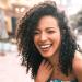Retrato de hermosa afroamericana latina confiada mujer riendo en la calle. Al aire libre.
