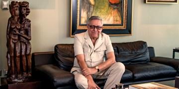 Pedro Malagón sentado en un sofá rodeado de piezas de su colección.