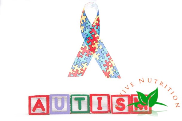 Autism awareness ribbon above letter blocks spelling autism on white background