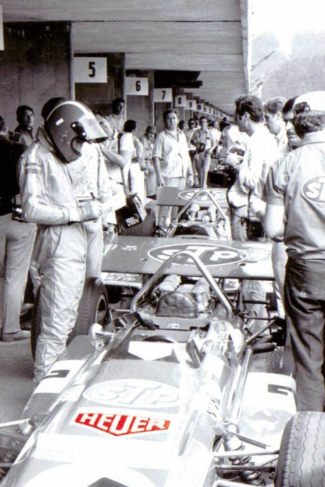Jo Siffert getting ready for a race, with Heuer logos on his suit and car