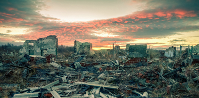 The remains of destroyed houses at sunset