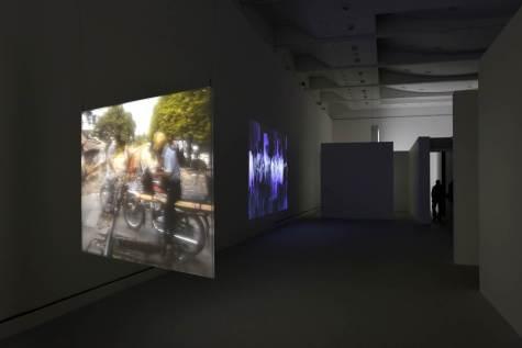 Fig. 7 : Vue de l'espace ouvert (dit l'Agora), exposition « Entrevoir. Robert Cahen ». De gauche à droite : La traversée du rail (2014), L'Entre (2014), © Nicolas Fussler.