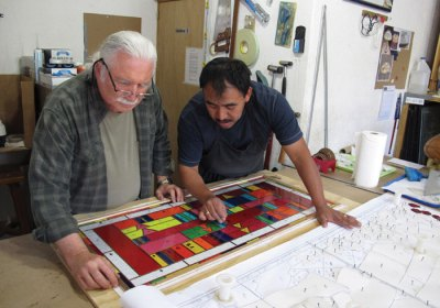 Lyn Hovey (left) checks the stained glass window with the printed plans
